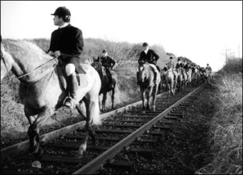 Mounted hunters on railway tracks